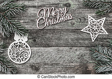 Upper, top, view from above of white winter figurines, evergreen branch and Merry Christmas inscription on gray background, with space for text writing, greeting.