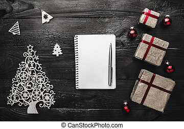 Upper, top, view from above of winter figurines, Christmas presents, notepad and pen on black background, with space for text writing, greeting.