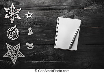 Upper, top, view from above of winter figurines, notepad and pen on black background, with space for text writing, greeting.