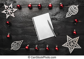 Upper, top, view from above, of wooden winter figurines, red toys notepad and pen on black background, with space for text writing, greeting.