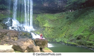 upper view girl on rock by waterfall in park