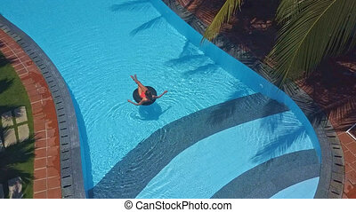 upper view girl swims on ring in swimming pool