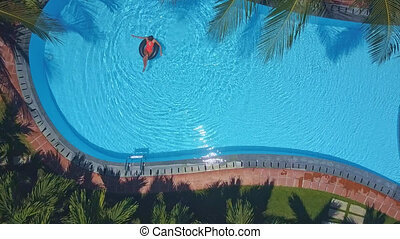 upper view girl whirls on ring in tropical pool