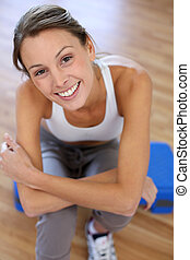 Upper view of cheerful girl sitting in gym