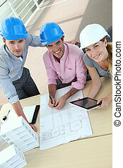 Upper view of team of architects working in office