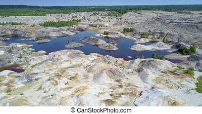 upper view old clay pit with lakes by forest under blue sky...