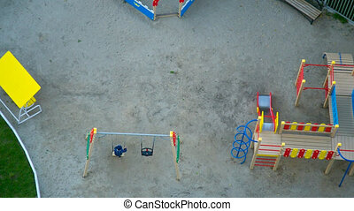 upper view playground with child on swing at maze and houses