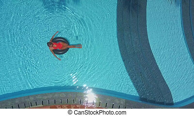 girl has good time swimming on buoy in pool - upper view...