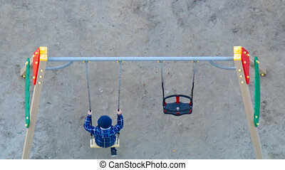 upper view schoolboy rocks on modern swing on playground
