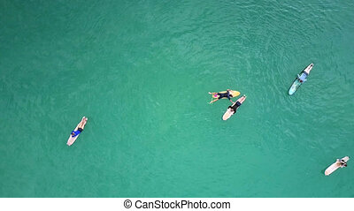upper view surfers lie resting on surfboards among ocean