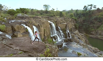 upper view woman on stone in yoga pose by waterfall