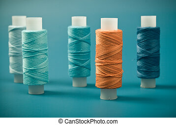 Upright colored spools of thread on a blue background