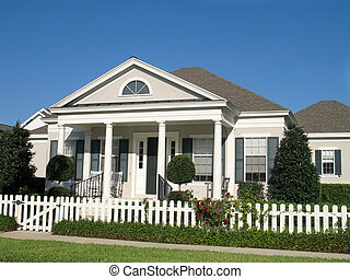 charming small town America cottage with picket fence around a lush lawn