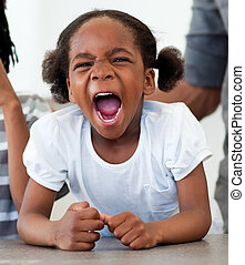 Upset Afro-american little girl screaming in the kitchen