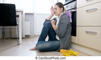 Upset and tired housewife crying on floor at kitchen