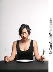 Upset asian woman sitting at the table