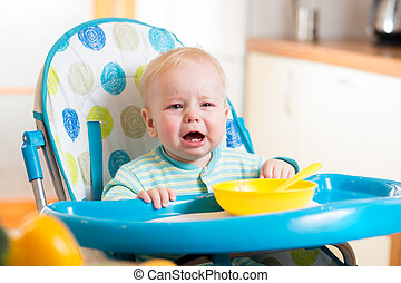upset baby sitting in highchair for feeding