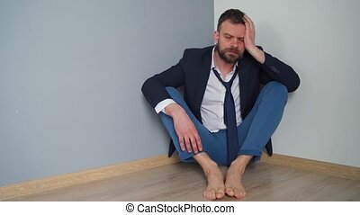 Upset bearded man in untidy formal clothes is sitting in an ...