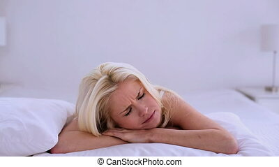 Upset blonde woman lying on her bed covering her head with a...