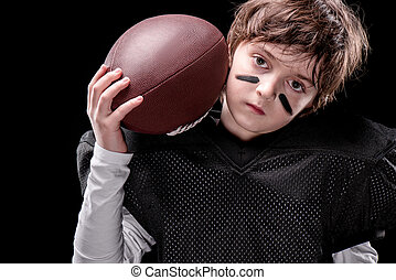 boy american football player holding rugby ball and looking at camera