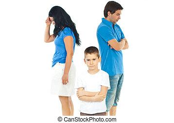 Upset boy between parents problems - Upset boy standing with...