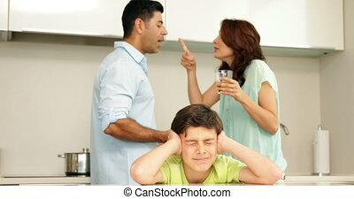 Upset boy covering his ears while his parents fight at home...