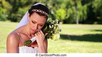 Upset bride sitting on the grass