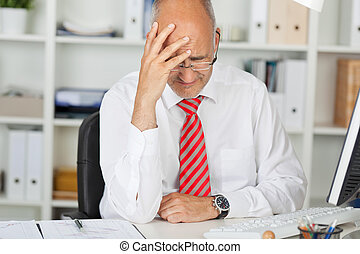 Upset Businessman With Hand On Head At Desk