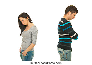 Upset couple in conflict standing back to back with arms...
