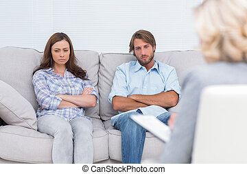 Upset couple sit on a sofa with arms crossed
