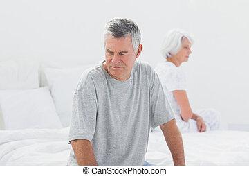 Upset couple sitting on bed
