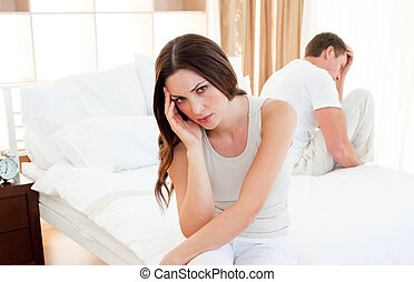 Upset couple sitting separately on their bed after an...