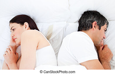 Upset couple sleeping in their bed separately after a row