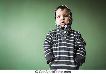 upset cute young boy holding hands in pockets