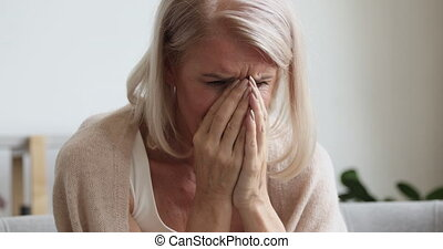 Upset depressed mature old woman crying alone at home ...