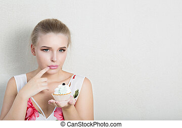 Upset dieting blonde lady holding sweet dessert with cream. Space for text