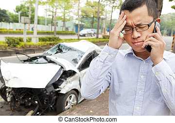 upset driver talking on mobile phone with crash car
