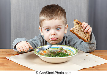 Upset face of little boy at the plate with soup