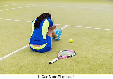Upset female tennis player is sitting on the court