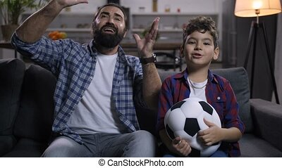 Upset football supporters watching soccer on tv