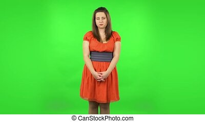 Upset girl shrugging and sighing. Chubby girl in a coral dress with straight hair medium length and light eyes on green screen at studio