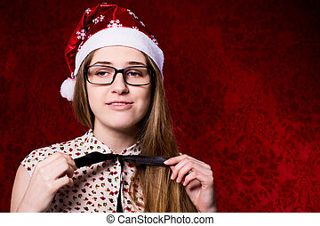 Upset girl with glasses in a santa hat on a red background