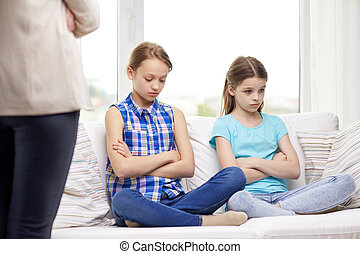upset guilty little girls sitting on sofa at home - people,...