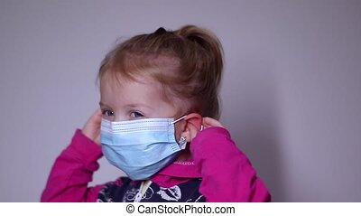 upset little blonde girl in a blue medical mask. takes off the mask. in a pink sweater. covid 19 pandemia. kids on isolation. FullHD footage