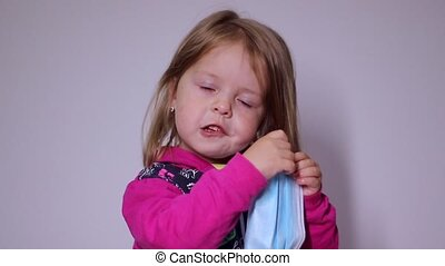 upset little blonde girl with a blue medical mask. trying to put it on. in a pink sweater. covid 19 pandemia. kids on isolation. FullHD footage.