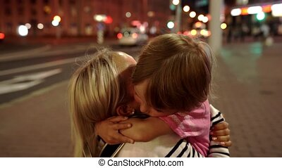 Upset little boy hugging his mother at night city with...
