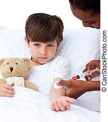 Upset little boy receiving an injection