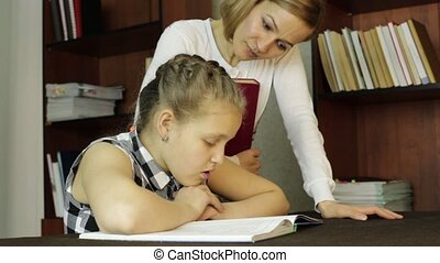 Upset little girl doing school tasks with mother, mom compels daughter to reads