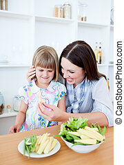 Upset little girl eating vegetables with her mother
