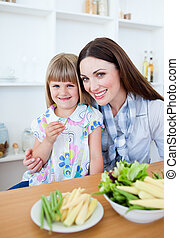 Upset little girl eating vegetables with her mother in the kitchen